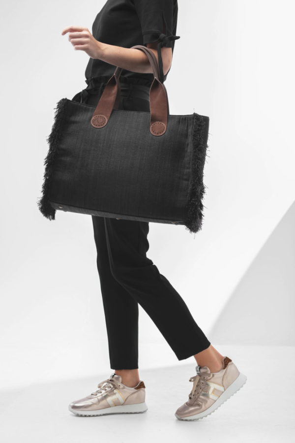 De Belle Large in Black Jeans staat stijlvol en vrouwelijk bij een zwarte outfit.